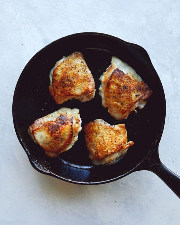 Chicken thighs in a skillet.