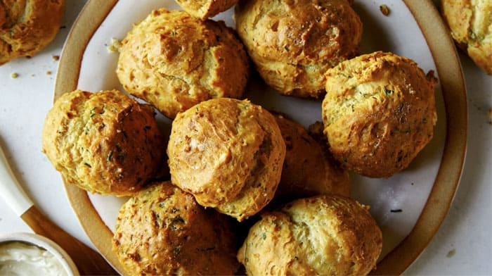 Drop biscuit recipe with sour cream and chives baked on a plate.