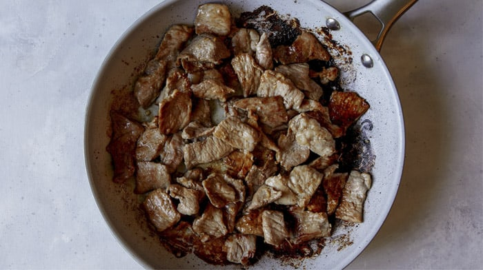 Pork cooking in a skillet for pad see ew.