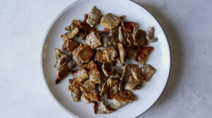 Cooked pork on a plate for pad see ew.