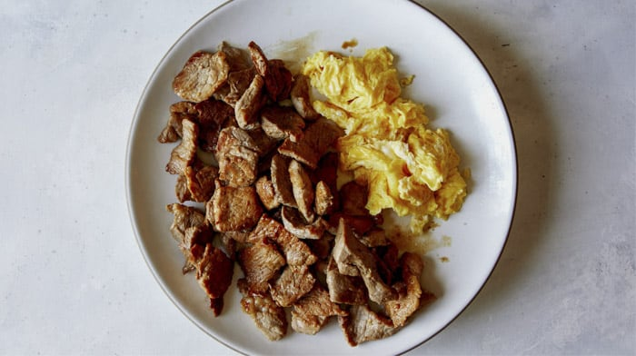 Cooked pork and eggs for pad see ew.