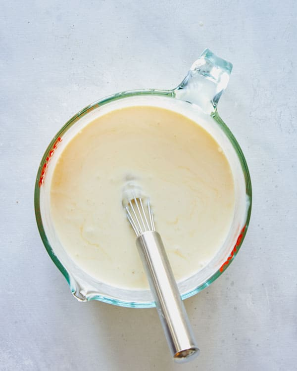 Eggs and cream whisked together in a bowl.