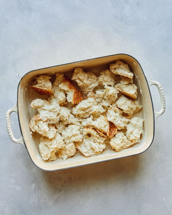 Torn bread in a baking dish for the base layer of a strata.