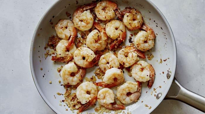 Shrimp being cooked in a skillet for shrimp scampi.