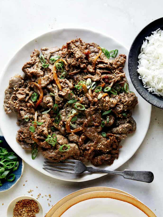 Korean beef bulgogi with rice on the side  and sesame seeds.