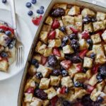 Berry bread pudding recipe being served onto plates.