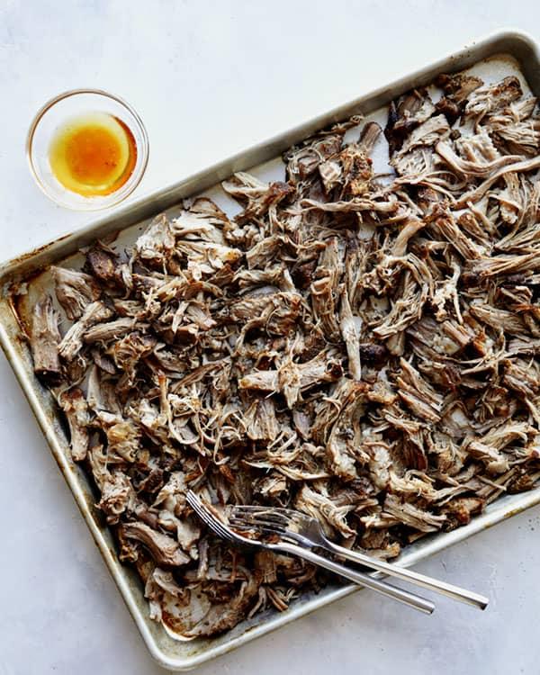 Carnitas recipe shredded on a baking sheet.
