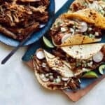 Carnitas recipe in a bowl next to a plate of tacos.