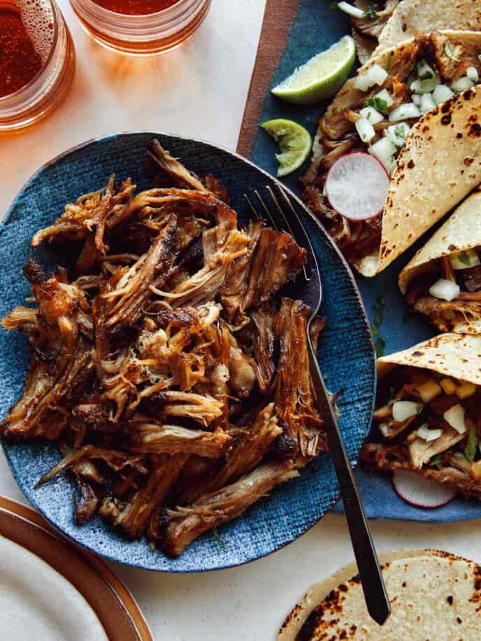 Carnitas being served with tacos and beer.