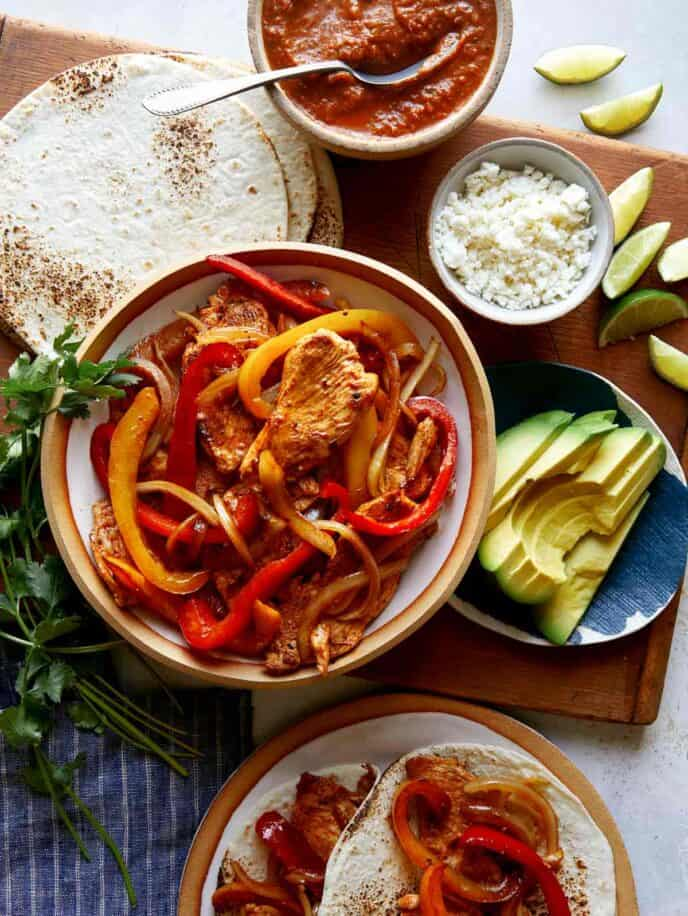 Chicken fajita recipe with toppings on the side.