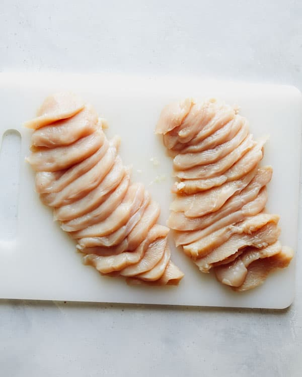 Chicken breast cut up on a cutting board.