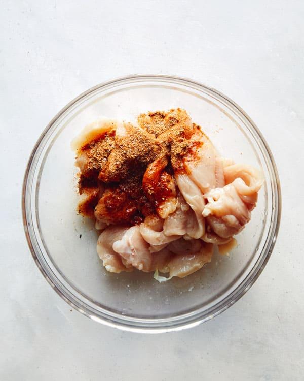 Chicken cut up in a bowl with fajita seasonings.