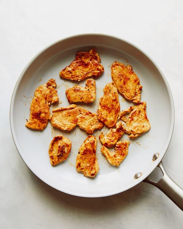 Chicken cooking in a skillet to make chicken fajitas.