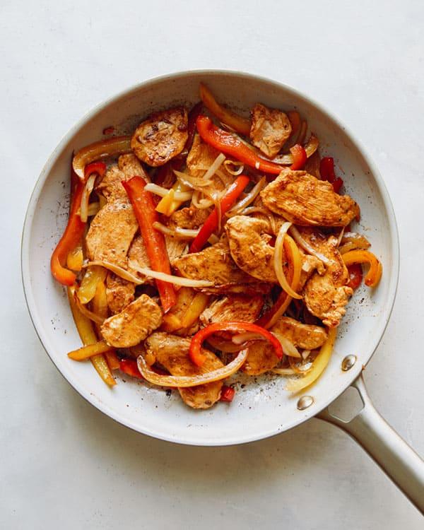 Chicken fajitas in skillet cooking.