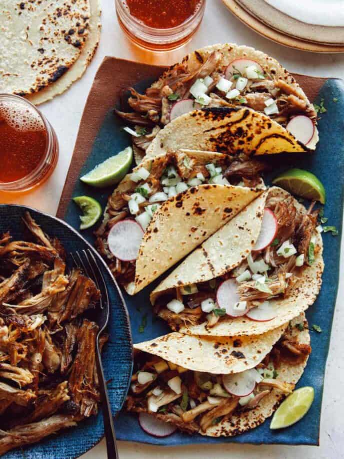 Easy carnitas recipe in a bowl next to a plate of tacos.