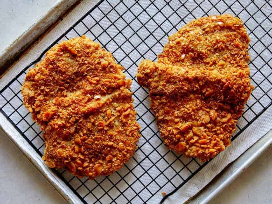 Freshly fried pork tenderloin cutlets on a baking sheet.