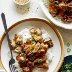 Honey garlic chicken dinner recipe with sesame seeds and green onions.