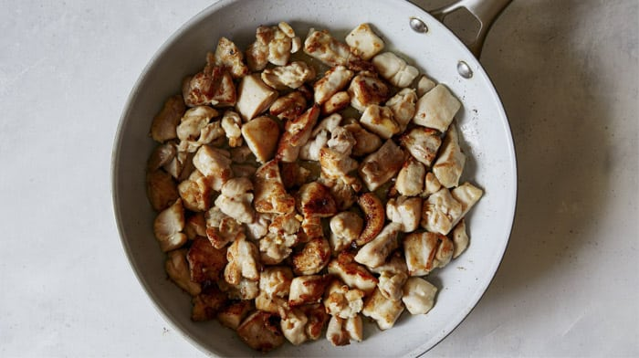 Chicken cooking in a skillet to make honey garlic chicken.
