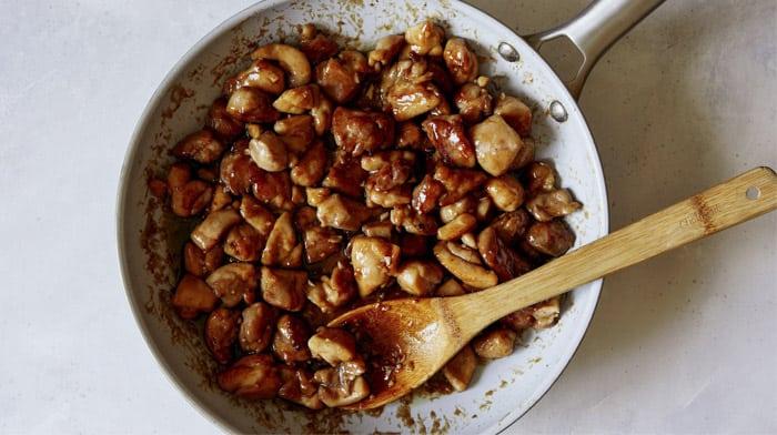 Honey garlic chicken in a skillet cooking.