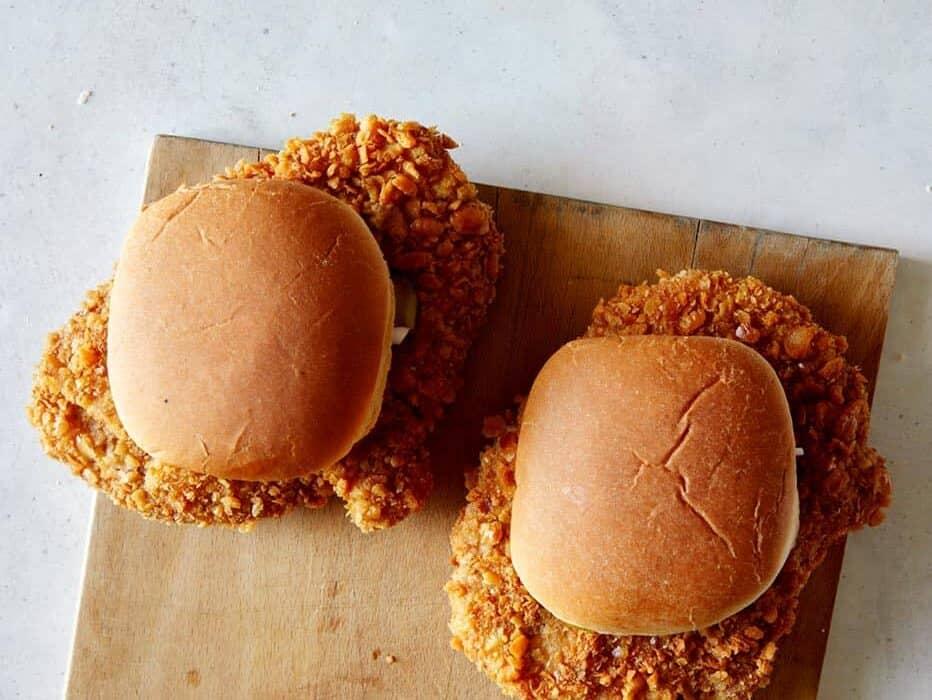 Overhead image of two pork tenderloin sandwiches on a cutting board.