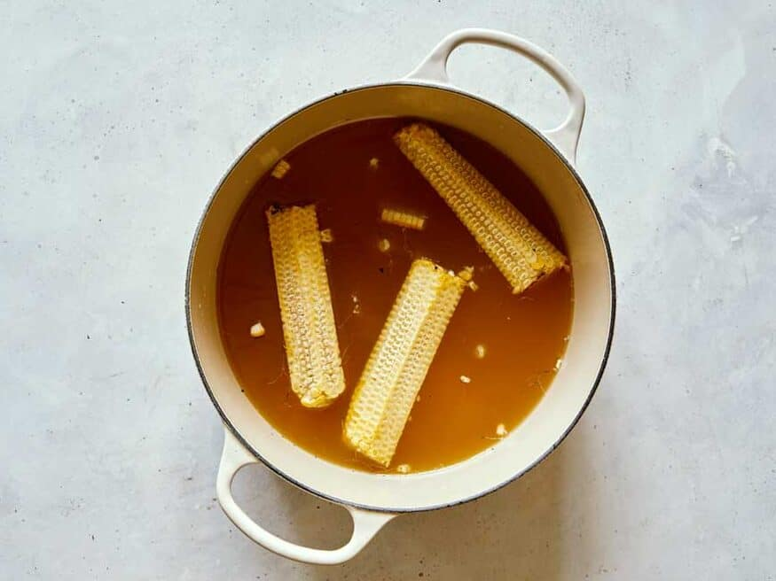 Corn on the cob simmering in stock to make corn chowder.