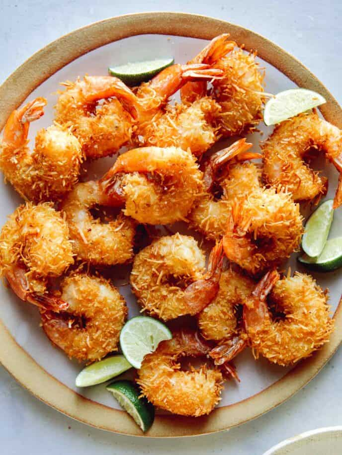 Coconut shrimp with lime wedges on a platter.