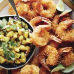Coconut shrimp on a platter with a bowl of mango salsa.