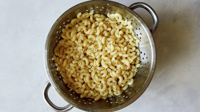 Cooked elbow macaroni in a colander.