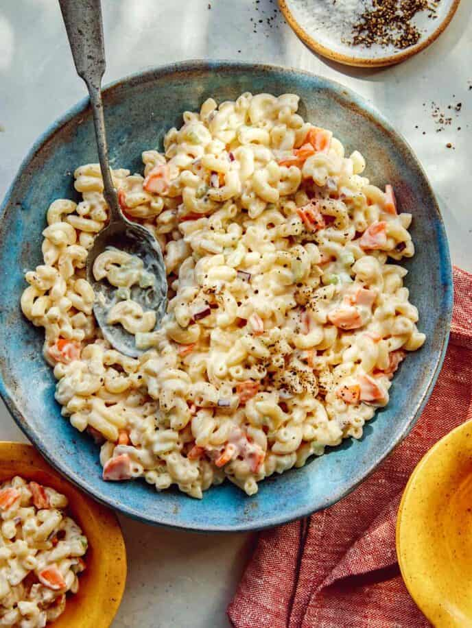 Hawaiian style macaroni salad in a bowl with serving bowls nearby.