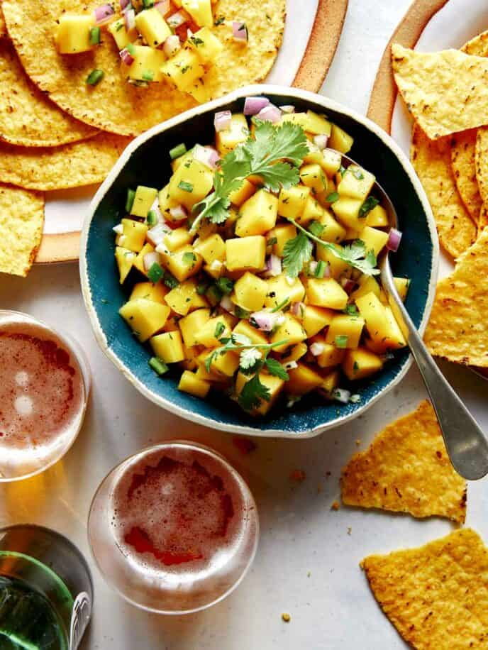 Mango salsa in a bowl with beer and chips.