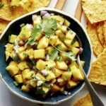 Mango salsa recipe in a bowl with chips.