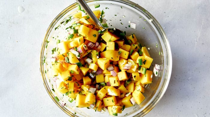 Mango salsa in a bowl mixed together.
