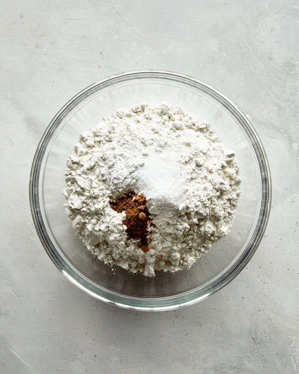 Adding dry ingredients to a bowl for old fashioned donuts.