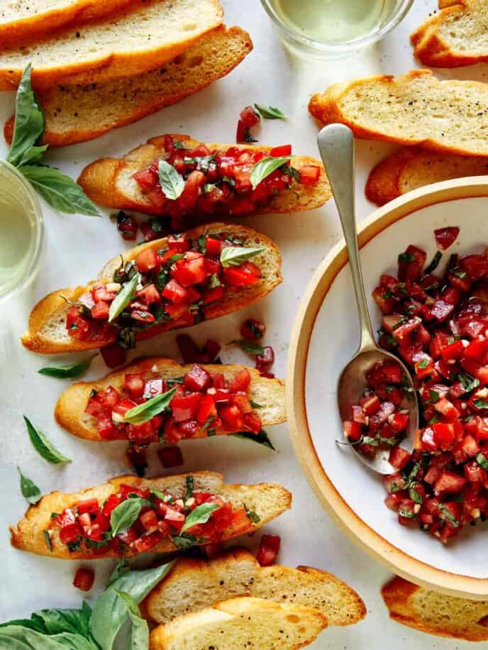 Brushetta ingredients on baguettes with basil on the side.