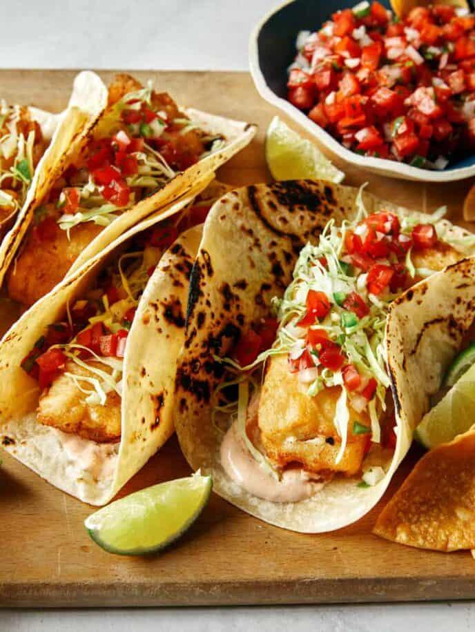 Baja fish tacos with limes and pico de gallo.