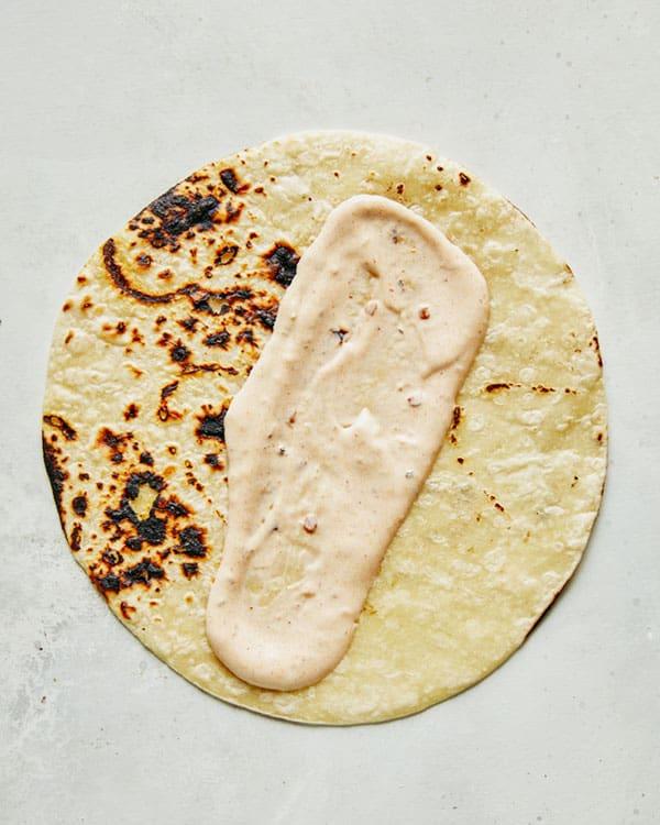 Making baja fish tacos with baja sauce.