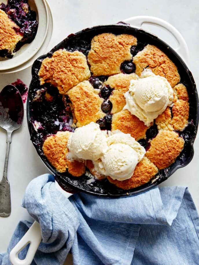 Blueberry cobbler recipe in a skillet with ice cream.