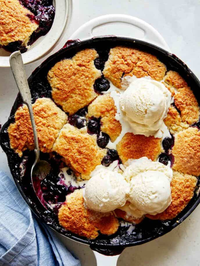 Blueberry cobbler recipe in a skillet with ice cream on top.
