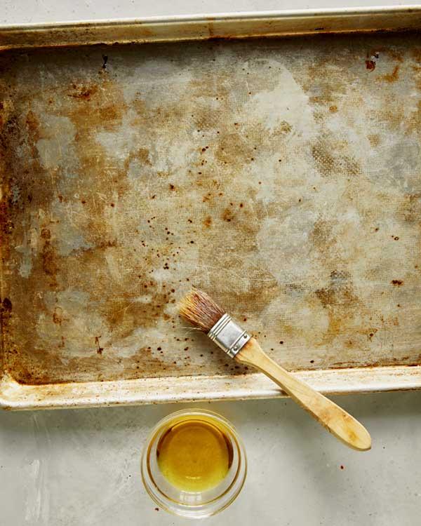 Oiling a baking sheet to toast bruschetta crostini.