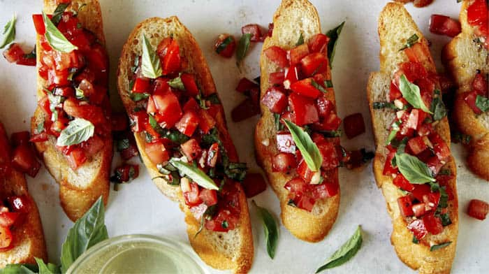 Bruschetta on toasted baguettes with basil.