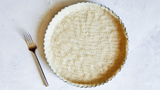 Tart dough pressed into a shell and pricked with a fork.