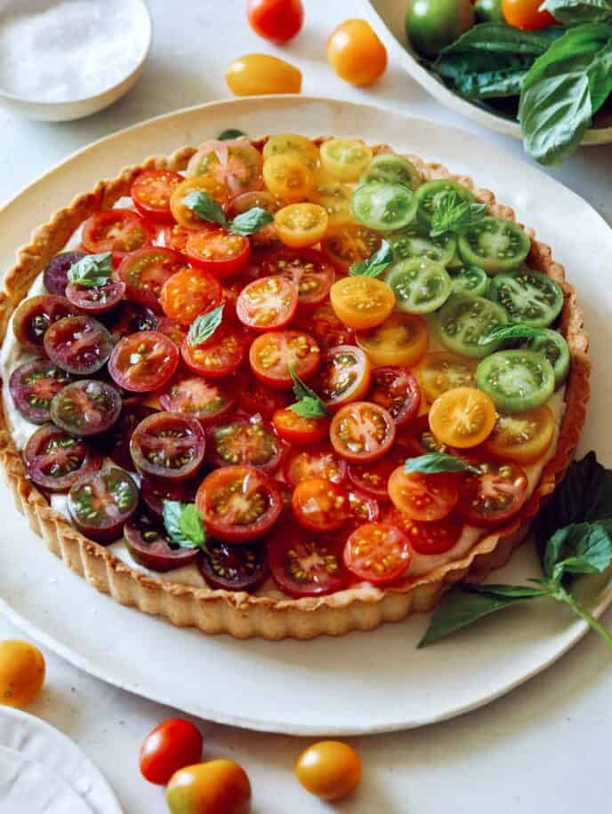 Heirloom tomato tart recipe on a plate with basil and salt in the background.