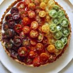 Tomato tart recipe on a platter with fresh tomatoes on the side.