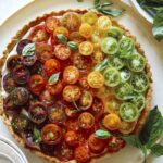 Heirloom tomato tart on a plate with fresh basil.