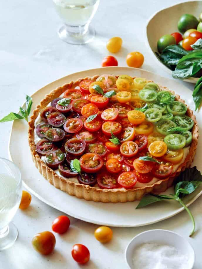 Tomato tart on a platter with white wine in the background.