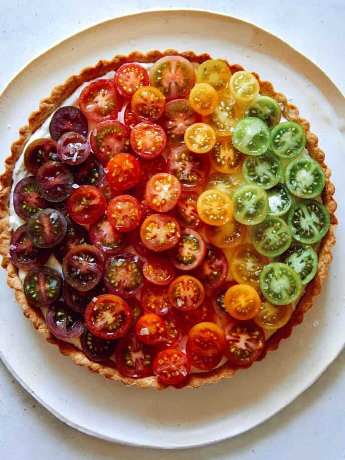 Close up on an ombre tomato tart with different colors of tomatoes.
