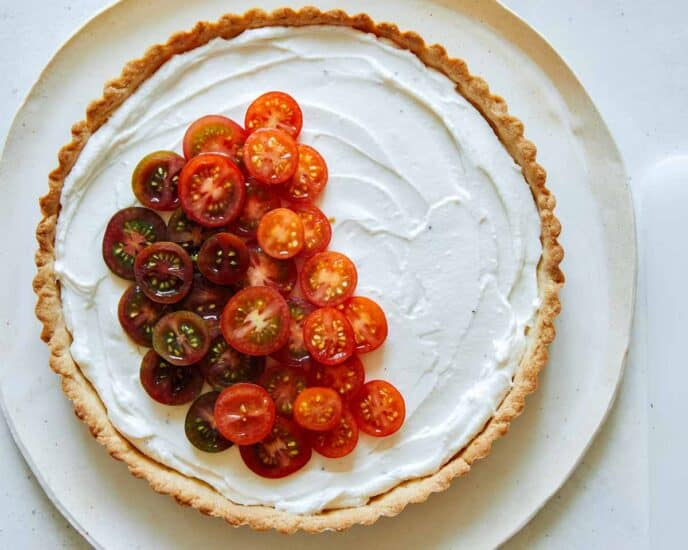 Heirloom tomato tart being filled with tomatoes.