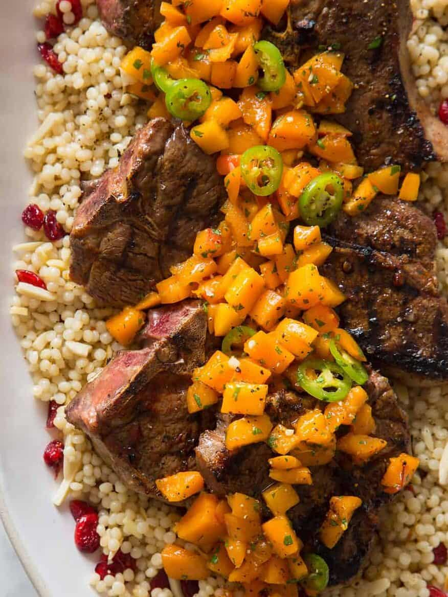 A close up of harissa grilled lamb chops with fresh apricot serrano salsa on couscous.