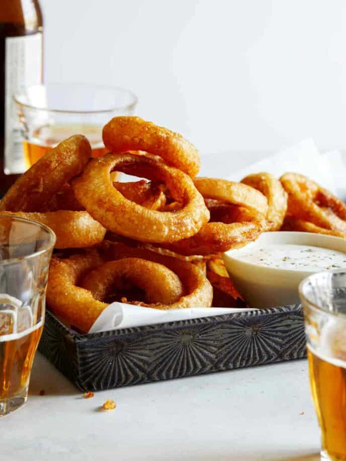 A tower of beer battered fried onion rings recipe with beer on the side.