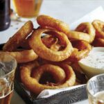 Beer battered fried onion rings with ranch dressing and beer on the side.